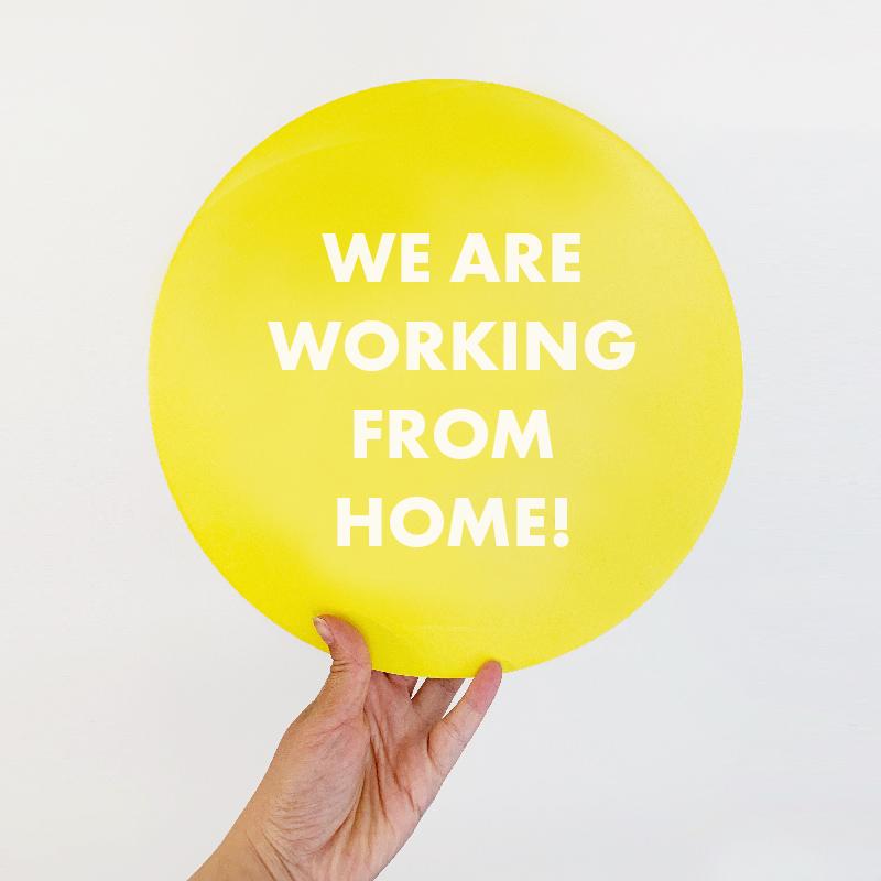 Hand som håller upp en skylt med texten: We are working from home